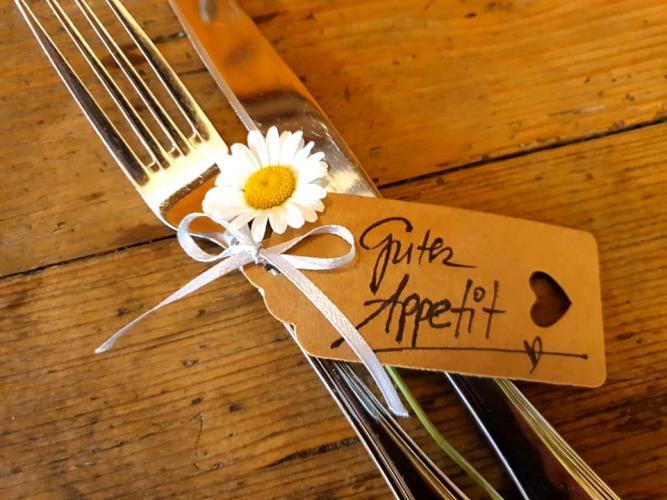 Besteck mit einer Blume und einem Schild mit dem Text: 'Guten Appetit!'